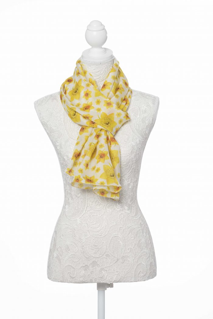 The beauty of nature is showcased magnificently in our generously sized oblong silk scarf. Digitally printed on silk from an original watercolour painting by a local artist, this design features classic yellow daffodils against a white background. Rolled and stitched edges. 100% silk. Presented tissue wrapped within an organza bag.